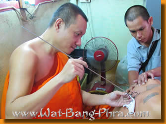 Here the monk etches a yant Paed Tidt Tattoo