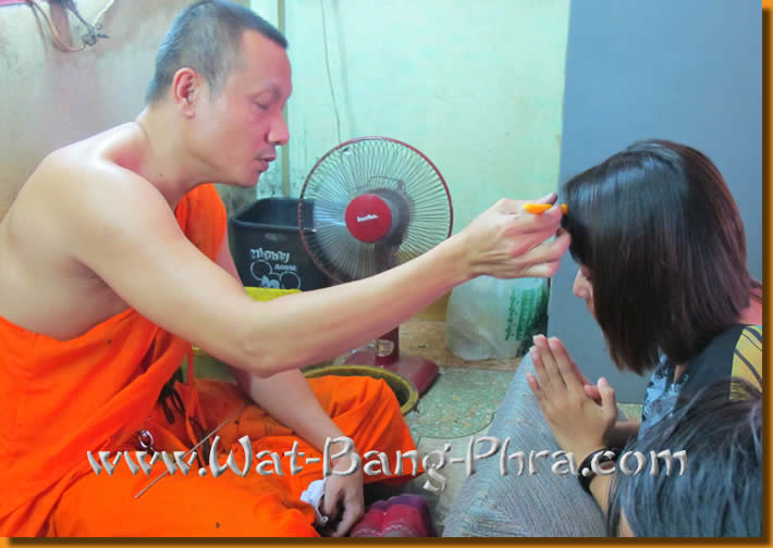 The monk Luang Pi Nunn is not allowed to touch a woman with his fingers. He takes a candle as extended hand